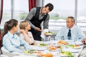 Group of successful businesspeople sitting and eating. Waiter is serving the food. The focus is on the waiter.