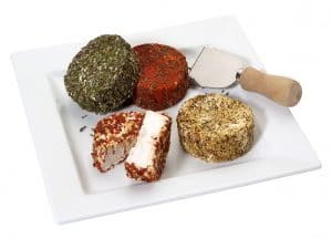 A platter with soft goat cheese covered with spices in different colors,isolated on white with clipping path.