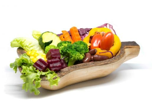 Salad in wooden bowl on white background